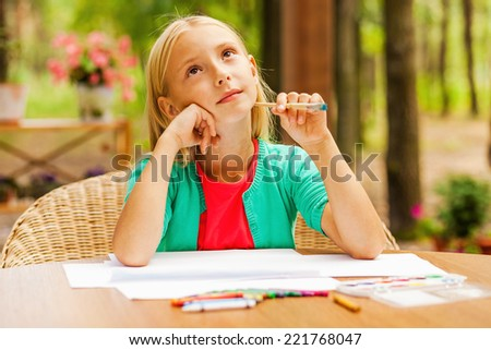Looking for inspiration. Thoughtful little girl holding hand on chin and looking away while sitting at the table with colorful pencils and paper laying on it - stock photo