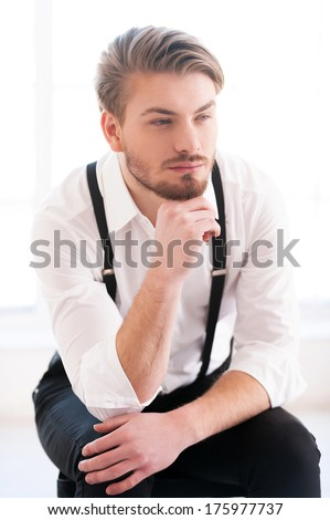 Looking for inspiration. Thoughtful young man in shirt and suspenders holding hand on chin and looking away while sitting on the chair - stock photo