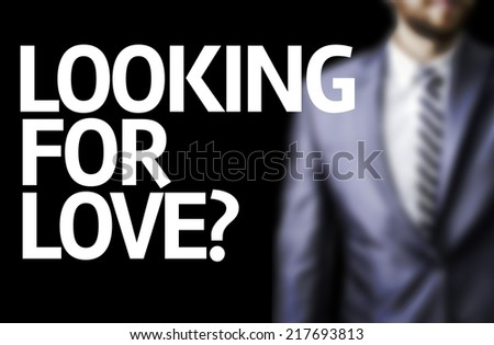Looking for Love? written on a board with a business man on background - stock photo