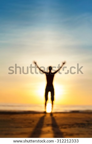Looking for the answer. Defocused blurred man phantom silhouette standing in rays of sunlight with raised up arms. Multicolored vibrant summertime outdoors image. Low point of view. - stock photo