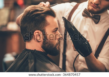 Looking good already. Close up side view of young bearded man getting groomed by hairdresser with hair dryer at barbershop - stock photo
