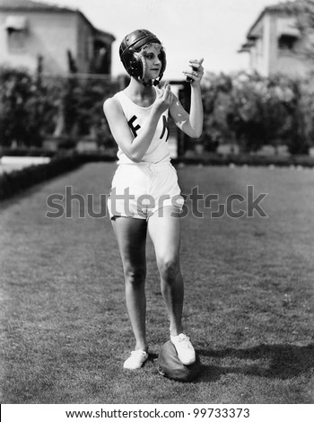 Looking good for the team, a young woman in a football helmet looking into a mirror and putting on make up - stock photo