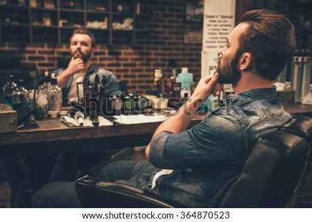 Looking good. Side view of handsome young bearded man looking at his reflection in the mirror and keeping hand on chin while sitting in chair at barbershop - stock photo