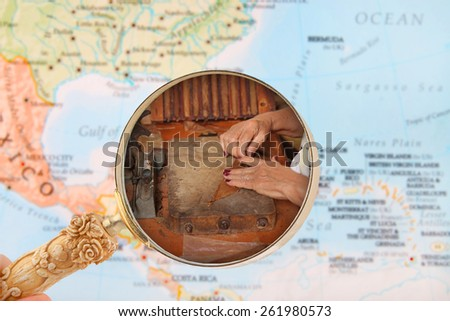 Looking in on a woman making cigars in Cuba with a map of the Caribbean - stock photo