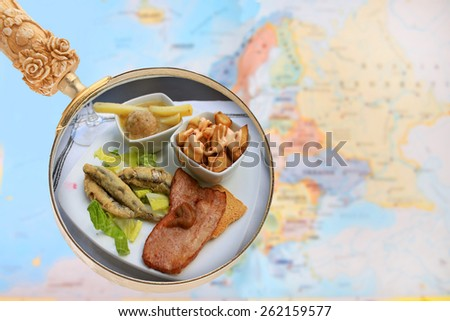 Looking in on food of the world showing tapas of Spain with a magnifying glass or loop with European map in the background - stock photo