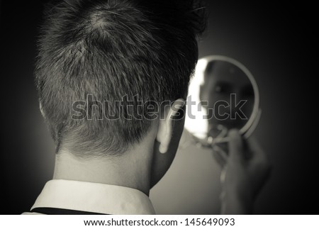 looking in the mirror and reflecting - stock photo