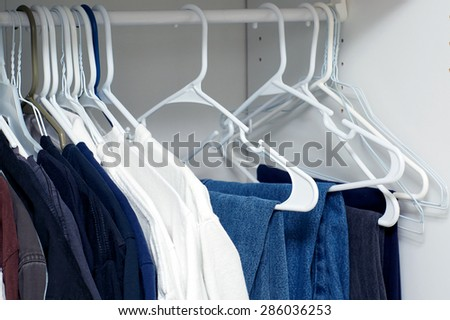 Looking inside a man's closet or armoire full of clothes hanging on hangers. - stock photo