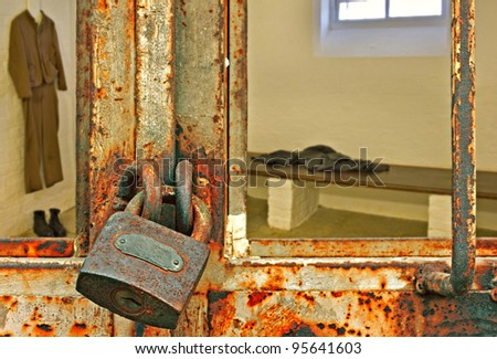 Looking into locked prison cell - stock photo
