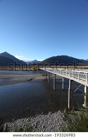 Looking north across the Mount White bridge over the Waimakariri river in the Arthurs Pass in the Southern Alps  region of New Zealand  - stock photo