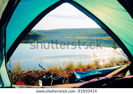 Looking out of open tent door upon calm lake in morning sunshine. - stock photo
