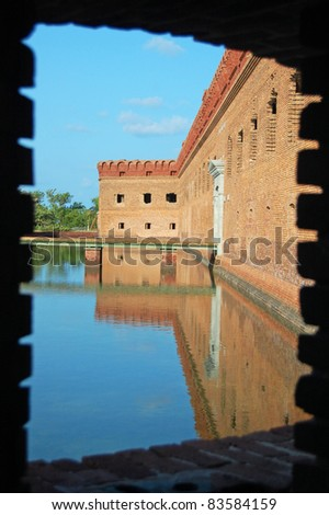 looking out of window along fort jefferson moat and fortification wall - stock photo