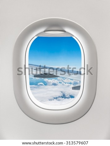 Looking out the window of a plane to the aircraft wing, blue sky and clouds - stock photo