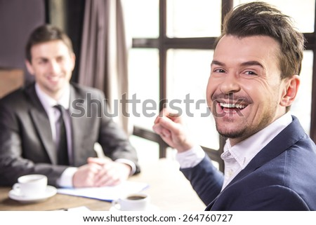 Looking over shoulder. Two young businessmen working during a business lunch and looking at camera. - stock photo