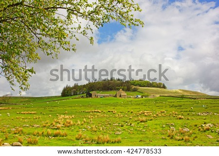Looking over the rugged landscape to a distant farm near to Crag Lough and views over the open countryside from Hadrian's Wall in spring, Northumberland, England, UK - stock photo