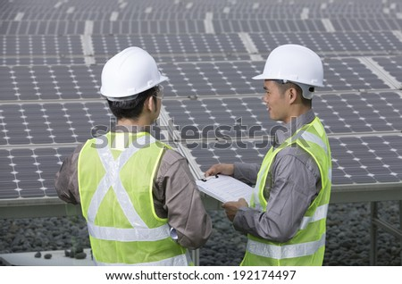 looking over the shoulder of two Chinese maintenance engineers discussing solar panels. - stock photo