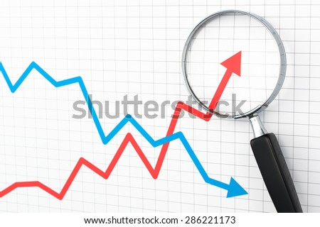 Looking positive result of line graph with magnifying glass. Line graph and magnifying glass.  - stock photo