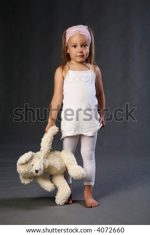 Looking sad and lonely preschool child holding teddybear in hand. - stock photo