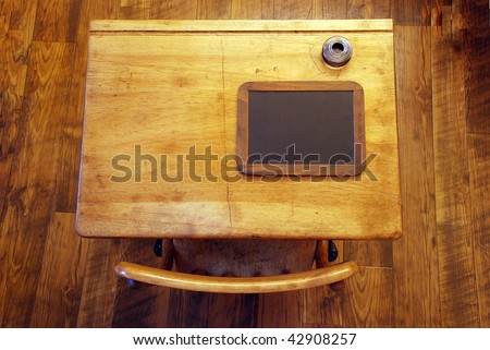 Looking straight down on an antique school desk isolated on a rough wooden floor.  Complete with ink bottle and small chalk board - stock photo