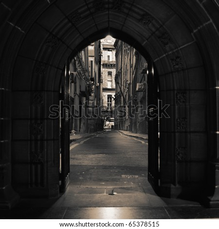 Looking through arched doors in ancient building towards dark alley - stock photo