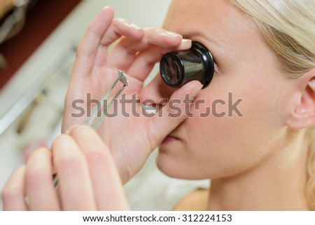 Looking through magnifying eye glass - stock photo