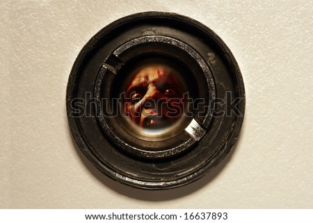 Looking through the peephole of an apartment door at an angry fellow on the other side. - stock photo