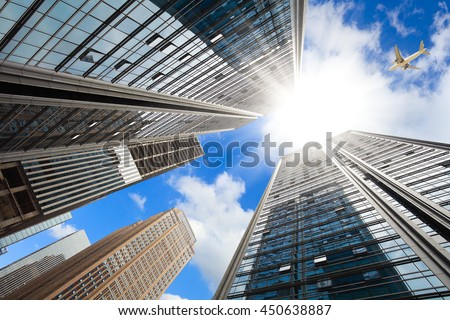Looking up Aircraft flying over the modern city skyscraper buildings backgrounds - stock photo