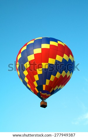 Looking up at a red, blue, and yellow hot air balloon as it soars and flies in the clear blue sky. - stock photo
