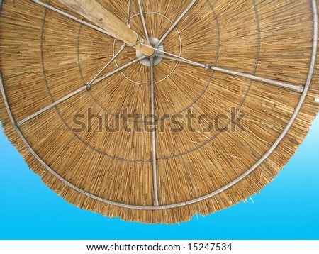 looking up at a straw beach umbrella - stock photo