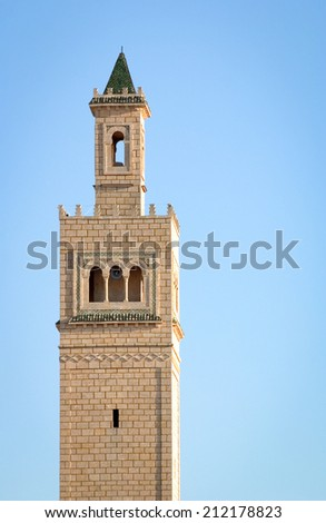 Looking up at a traditional minaret tower, a distinctive architectural feature of mosques. - stock photo