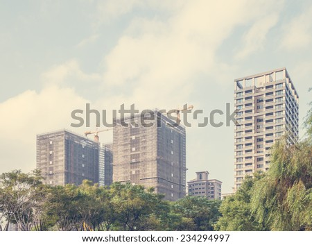 Looking Up at High Rise Buildings Under Construction as part of Urban Skyline with Tree Tops - stock photo