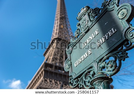 Looking up at the Avenue Gustave Eiffel sign with the Eiffel Tower behind. - stock photo