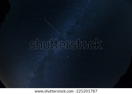 Looking up at the night sky and airplane trail - stock photo