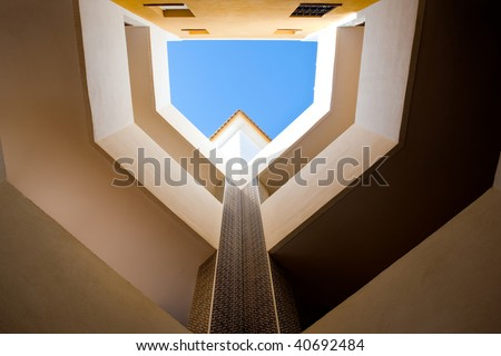 Looking up in a European style courtyard with natural light. - stock photo