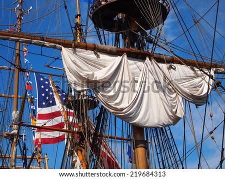 Looking up into the rigging and masts of a tall ship, a rolled up sail, a large American flag and many small international flags can be seen against a vibrant blue sky.  - stock photo