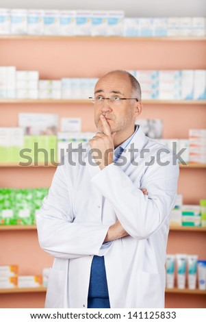 Looking up pharmacist thinking over the medicine backgrounds - stock photo