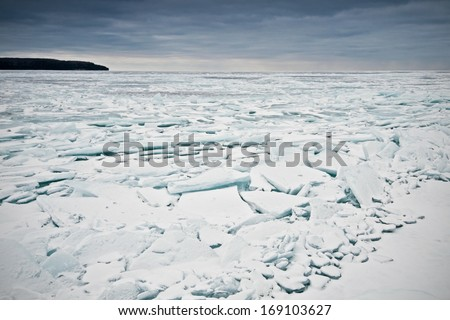 Looking west from Gills Rock across the ice flows in Green Bay on a cold winter afternoon in Door County, Wisconsin. - stock photo