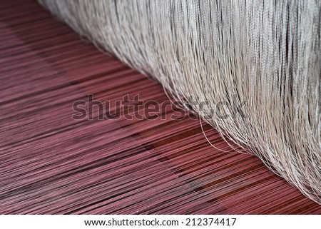 Loom weaver working with an old wooden weaving shuttle on the warp - stock photo