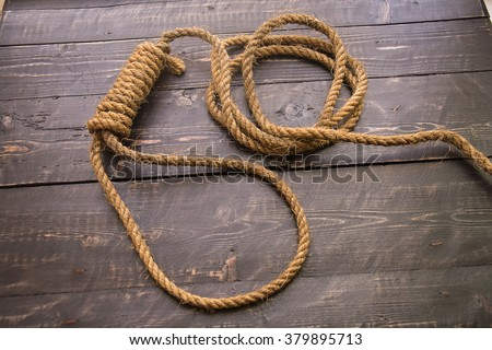 Loop hempen rope on on a dark wood tables background. Running knot. - stock photo