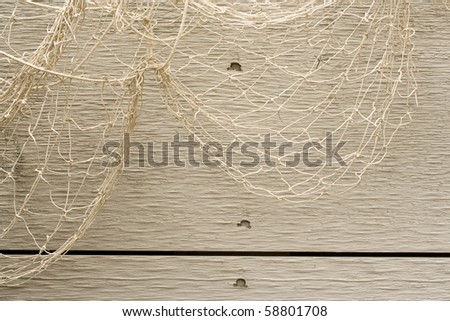 Looped fish net over weathered boards. - stock photo