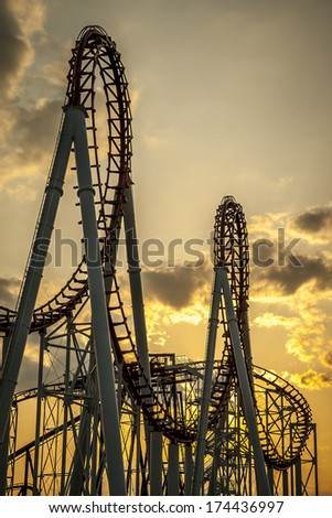 Loops of a roller Coaster at Sunset. - stock photo