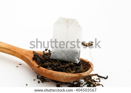 loose green tea, tea bag and a wooden spoon on a white background   - stock photo