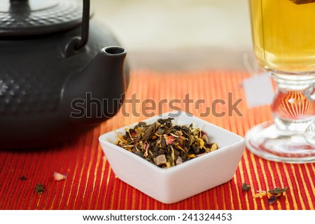 Loose leaf tea with tea pot and glass cup. Shallow depth of field. Focus on tea leaves - stock photo