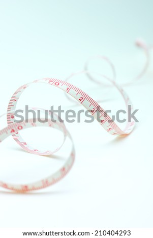 loosely curled and extending measurement tape with red markings.  - stock photo