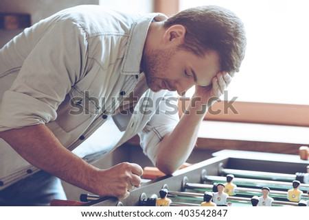 Looser. Desperate young man keeping his hand on forehead while standing over foosball in front of window - stock photo