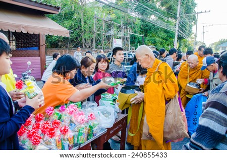 LOPBURI, THAILAND - JANUARY 1:Thai people give food offerings to a Buddhist monk on 1 January, 2015 in Lopburi, Thailand. Buddhist Thai traditional, people will make merit making by give food to monk. - stock photo