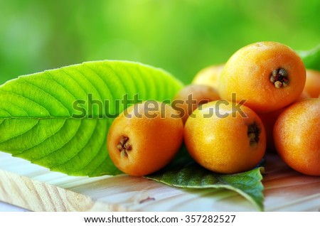 Loquat Medlar fruit on a green background - stock photo