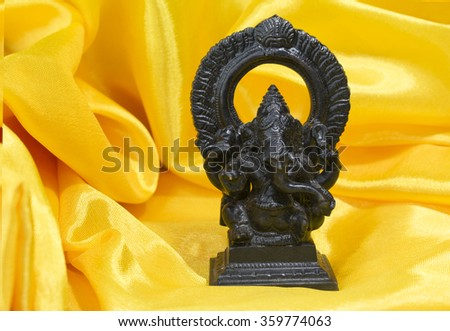 Lord Ganesha black idol on the yellow background - stock photo