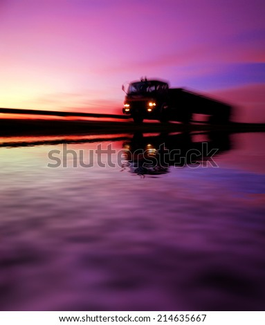 lorry at highway during sunset reflected on water. motion blur effects. - stock photo