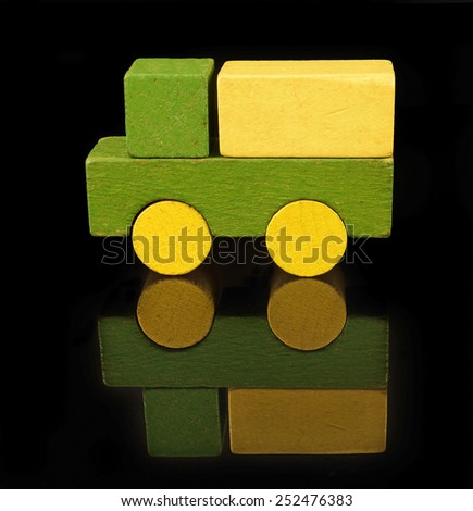 Lorry of wooden blocks, traditional toy on black background - stock photo