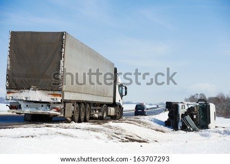 Lorry trailer car crash smash accident on an slippery winter snow interstate road - stock photo